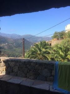 Photo d'un muret en pierres taillées dans un paysage de ciel bleu, de montagnes et de palmiers. Un paysage essentiel