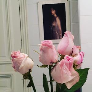 Photo d'un petit bouquet de roses devant un portrait de femme