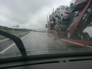 Photo d'une route droite par un temps gris et pluvieux prise depuis la place du conducteur d'une voiture regardant à travers son pare-brise avant