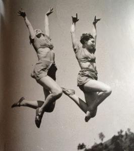 Photo de deux jeunes femmes sautant en l'air les bras levés au ciel