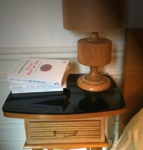 Photo d'une table de chevet avec des livres et une lampe
