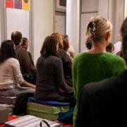 Photo d'ensemble de pratiquants vus de dos méditant sur coussin dans une salle
