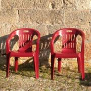 Photo de deux chaises en plastique rouges posées devant un mur de pierres taillées