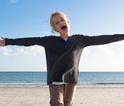Photo de face d'un enfant sur une plage, debout, les bras écartés à l'horizontal