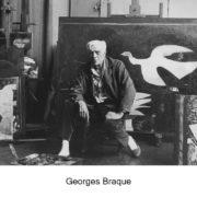 Photo noir et blanc de Georges Braque assis dans son atelier, devant certains de ses tableaux