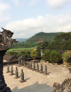 Photo en plongée d'une cour en pierre où sont alignées deux rangées de statues, avec à gauche au premier plan la sculpture d'un dragon