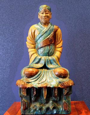 Image d'une scupture de méditant chinois, de couleur bois clair et jade sur un fond bleu