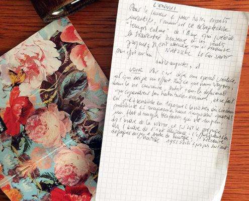 Photo en gros plan d'une lettre posée en partie sur un cahier à fleur, à plat sur un bureau deviné
