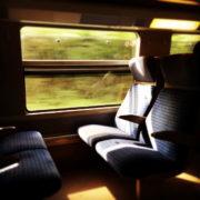 Photo de l'intérieur d'un TGV, la lumière éclairant deux places assises à travers la vitre