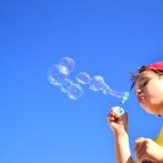 Photo d'un enfant faisant des bulles sur un fond ciel azur