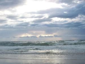 Photo d'une plage de sable que viennent battre des vagues sous un ciel nuageux percé par les rayons du soleil