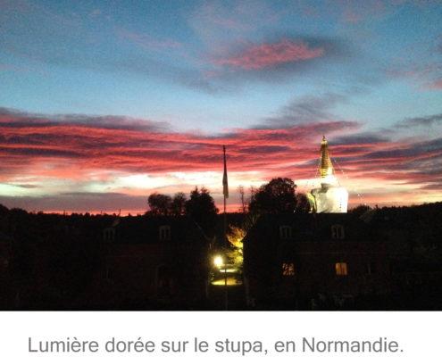 Photo du stupa de Vajradharaling, en Normandie, dans un ciel bleu orné de nuages gris, roses et blancs, et baigné dans la lumière