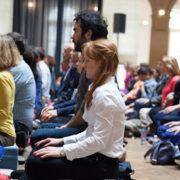 Photo de pratiquants, avec Maude en premier plan, prise par Claire Cocano à l'occasion d'un évènement de l'École occidentale de méditation fondée par Fabrice Midal
