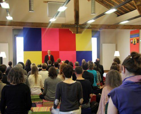 Photo de Fabrice Midal, fondateur de l'École occidentale de méditation, enseignant devant un public nombreux lors d'un weekend à Genève