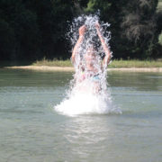 Photo d'une personne se baignant dans un lac et s'aspergeant d'eau