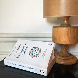 Photo d'une table de chevet avec un livre et une lampe