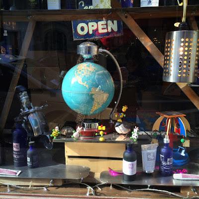 """Photo d'un globe terrestre entouré de divers objets, posés sur une table, un signe """"open"""" placé juste au-dessus"""