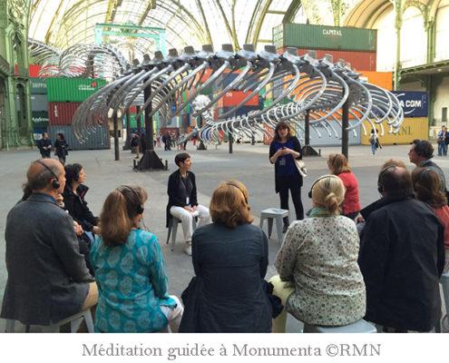Photo d'une séance de méditation guidée, avec Clarisse Gardet, intervenante au sein de l'École occidentale de méditation, fondée par Fabrice Midal, assise de trois quart et une douzaine de participants assis en demi-cercle en face d'elle