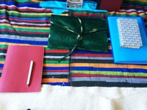 Photo de divers petits objets de couleur posés sur un tissus rayé de multiples couleurs