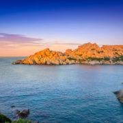 Photo aux couleurs saturées d'une étendue d'eau bleue et d'un bout de terre orangée, sous un ciel indigo, blanc et rose