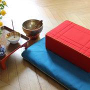 Photo d'un coussin de méditation rouge sur un tapis turquoise, avec à gauche, un petit gong et une petite table sur laquelle sont posés des fleurs en vase et un bol à encens