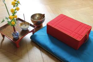Photo d'un coussin de méditation rouge posé sur un tapis de méditation turquoise