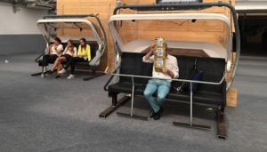 Photo d'un homme assis, lisant un dépliant lui cachant le visage, attendant son moyen de transport