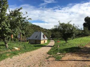 Photo d'un chemin de terre dans la nature au bord gauche duquel, un peu plus loin, se trouve une petite maison