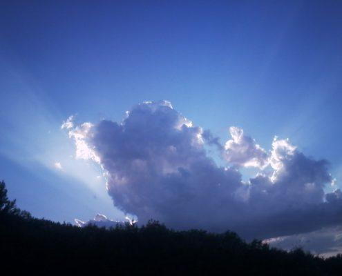 Photo d'un grand nuage, dans un ciel à diverses nuances de bleu, des bords duquel jaillissent des rayons de lumière