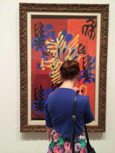 Photo d'une femme, de dos, regardant un tableau