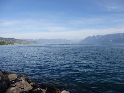 Photo de la mer, calme sous un ciel bleu agrémenté de quelques nuages blancs à l'horizon