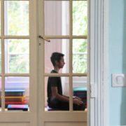 Photo de Pablo, de profil, pratiquant la méditation derrière une porte vitrée