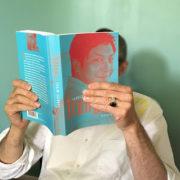 Photo d'un homme lisant la biographie de Trungpa par Fabrice Midal, fondateur de l'École occidentale de méditation, le visage caché par la couverture du livre où figure un image de Trungpa souriant
