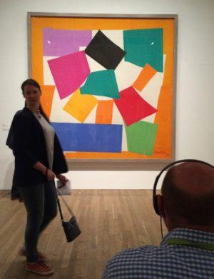 """Photo du tableau """"L'escargot"""" de Matisse, avec au premier plan, à droite, un homme assis avec des écouteurs et à gauche, une femme, la tête tournée vers l'objectif"""