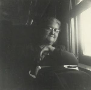 Phot noir et blanc d'une femme âgée, assise de face près d'une fenêtre