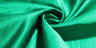 Photo en gros plan d'un tissu vert émeraude formant une spirale