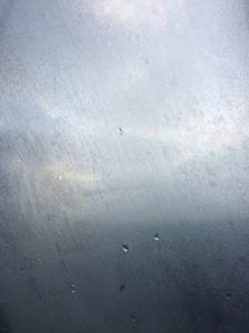 Photo d'un ciel de mauvais temps vu à travers une vitre sur laquelle coulent quelques gouttes de pluie