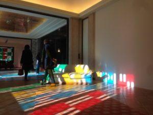 Photo d'une pièce, dans la pénombre, une partie du sol éclairé par la lumière extérieure formant une mosaïque de couleurs