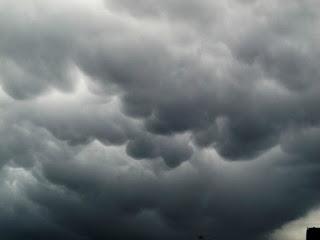 Image d'un ciel lourd, entièrement couvert de nuages noirs et gris