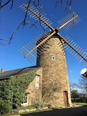 Photo d'un beau moulin de pierre encadré d'un ciel bleu intense