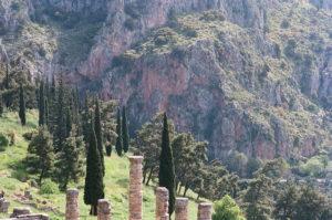 Superbe photo avec au premier plan les colonnes et vestiges en pierres d'un ancien édifice, dans un cadre naturel de collines boisées et de roches rouges