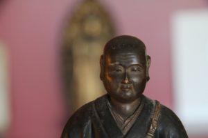 Image du buste d'une sculpture de bouddha, devant un arrière-plan flou