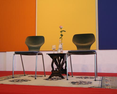 Photographie de deux chaises sur un tapis séparées par une table sur laquelle repose un soliflore avec une rose.