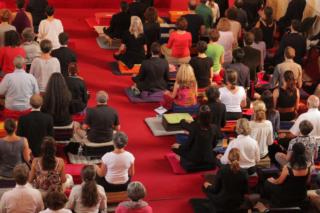 Photo d'une grande salle de pratique remplie de méditants