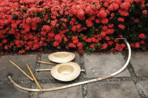 Photos de 2 chapeaux posés au sol, arrière plan de fleurs roses