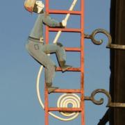Photo d'une oeuvre de ferraillerie représentant un pompier sur une grand échelle