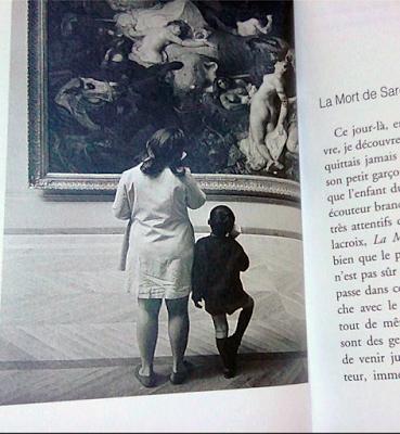 Photo noir et blanc de Willy Ronis montrant une femme en blanc et un enfant en noir de dos, regardant un tableau