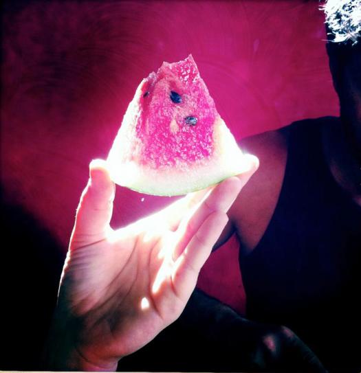 Photo d'une part de pastèque tenue dans un rayon de soleil