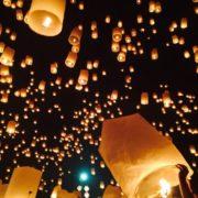 Photographie montrant des lanternes volantes s'élevant dans le ciel de nuit.