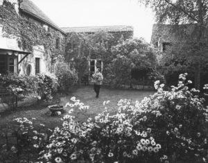 Photographie en noir et blanc où l'on voir Barbara marcher devant une maison de campagne au milieu d'un jardin en fleurs.